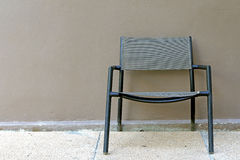 En enkel stol med en cementväggbakgrund Fotografering för Bildbyråer
