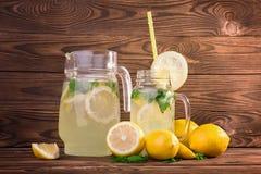 En enorm kanna och en muraretillbringare av uppfriskande lemonad eller mojito Sommarcoctailar med citroner och den gröna mintkara Arkivfoton
