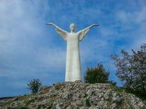 En enorm snövit staty av Kristus på överkanten av ett berg mot en blå himmel och moln i Maratea, Basilicata, Italien royaltyfri fotografi