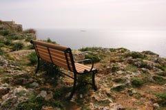 En ensam bänk på en stenig havkust Arkivfoto