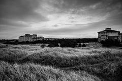 En ensam byggnad på horisonten bak ett stort fält av högväxt gräs i stormen i Long Beach Washington i svartvitt arkivbild