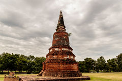 En ensam Chedi pagod under en stormig himmel i Auytthaya, Thailand Royaltyfri Bild