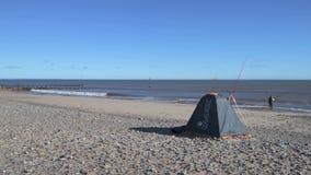En ensam fiskare går och gjuter av för att fiska i havet på den Hornsea sjösidan lager videofilmer