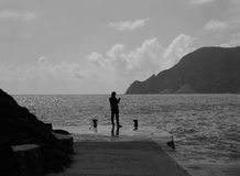 En ensam fiskare på den italienska kusten Arkivbild