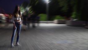 En ensam flicka med iklätt långt hår en blus och jeansställningar i fyrkanten i aftonen bland det gå folket stock video