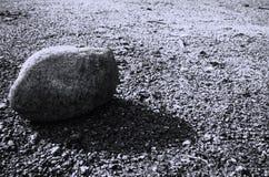 En ensam grå färgsten gjuter en skugga i svartvitt Royaltyfri Foto