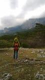 En ensam handelsresande står på kullen och ser bergen Molnigt mörkt väder arkivbild