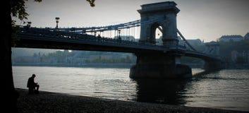 En ensam konstnär som sitter nära bron arkivfoto