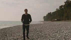 En ensam man strosar längs en stenig strand, vågor slår mot kusten stock video