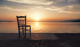 En ensam stol på havet på solnedgången Royaltyfri Bild