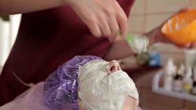 En erfaren cosmetologist f?rbereder en sund maskering f?r klienten Hon f?r upp och trycker p? framsidan med en borste A lager videofilmer