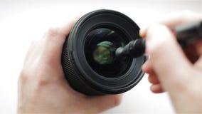 En erfaren fotograf- eller videooperatör gör intensivt ren det främre exponeringsglaset av den fotografiska linsen från smuts och lager videofilmer