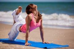 En essayant un nouveau yoga posez à la plage Images libres de droits