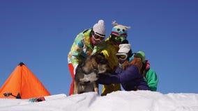 En este vídeo usted puede ver como cuatro personas jovenes hermosas se divierte en la parte superior de la montaña de la nieve metrajes