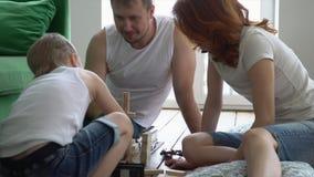 En este vídeo usted puede ver mientras que la familia de los jóvenes juega en casa en una torre de madera del piso La familia jue metrajes