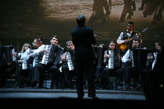 En etapa, los músicos y los solistas de la orquesta de los acordeonistas (orquesta armónica) debajo del bastón del conductor Foto de archivo libre de regalías