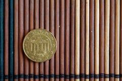 En euromyntlögn på träbambutabellvalör är cent för euro tio - tillbaka sida Arkivfoton