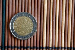 En euromyntlögn på träbambutabellvalör är 2 euro - tillbaka sida Royaltyfri Bild