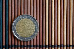 En euromyntlögn på träbambutabellvalör är två euro - tillbaka sida Arkivfoto