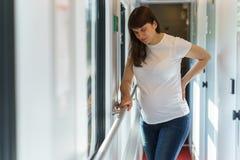 En europeisk gravid kvinna i t-skjorta får tillbaka smärtar, medan resa vid järnvägen Arkivbild
