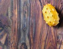 En exotisk kiwanofrukt på det övre högra av träbakgrund arkivbild