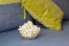 En exponeringsglasbunke av popcorn Aftonslags tv?sittssoffa som h?ller ?gonen p? en film eller TV-serie hemma arkivfoto