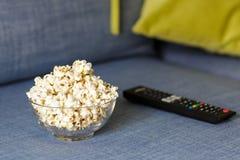 En exponeringsglasbunke av popcorn och fj?rrkontroll Aftonslags tv?sittssoffa som h?ller ?gonen p? en film eller TV-serie hemma fotografering för bildbyråer