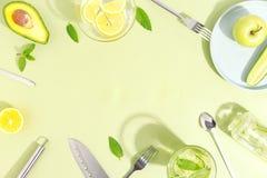 En exponeringsglasdryckeskärl, en flaska av gurkavatten, frukter och bestick på ett ljust - grön bakgrund Minimalistic idérikt be arkivfoto