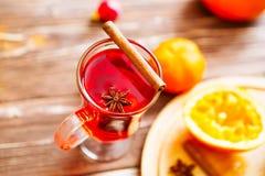 En exponeringsglaskopp av jul funderade vin eller gluhwein med kryddor och orange skivor på den lantliga trätabellen arkivfoto