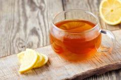 En exponeringsglaskopp te med citronen på den trälantliga tabellen royaltyfri bild
