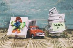 en exponeringsglaskrus i hennes mynt, en leksakbil, en gåvaask Begreppet gör en insättning i banken och segrar en bil där tonar royaltyfria bilder