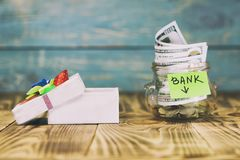 en exponeringsglaskrus i hennes mynt, en leksakbil, en gåvaask Begreppet gör en insättning i banken och segrar priset där tonar royaltyfri foto