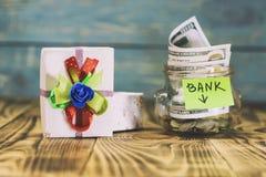 en exponeringsglaskrus i hennes mynt, en leksakbil, en gåvaask Begreppet gör en insättning i banken och segrar priset där tonar royaltyfria foton