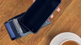 En extrem närbild på en lattekopp en NFC-terminal med en smartphone arkivfilmer