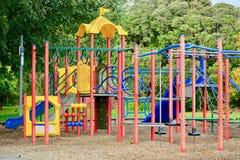 En färgglad lekplats, inviterande ungar som där spelar Kombinationslekplatsstruktur för småbarn inklusive glidbanor, klättrare arkivbilder