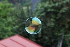 En färgrik bubbla som skapas av bubblablåsaren I härligt cirkelflyg i luften och på bakgrunden finns det träd och taket royaltyfri fotografi