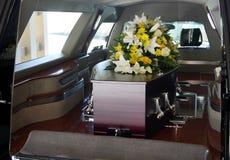 En färgrik casket i en likvagn eller kyrka för begravning arkivbild