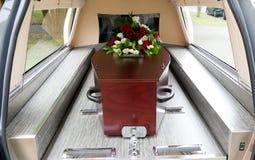 En färgrik casket i en likvagn för begravning arkivfoton