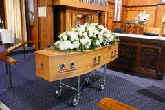 En färgrik casket i en likvagn eller kapell för begravning eller jordfästning på kyrkogården arkivbilder
