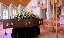 En färgrik casket i en likvagn eller kapell för begravning eller jordfästning på kyrkogården royaltyfri foto