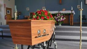En färgrik casket i en likvagn eller kapell för begravning eller jordfästning på kyrkogården royaltyfri bild