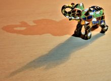 En färgrik keramisk elefant med dess skuggor reflekterade på golvet Royaltyfri Fotografi