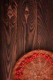 En färgrik partisk sammansättning är i det lägre högra hörnet av en brun korg med den saftiga röda vinbäret på en trätabell för m Arkivbilder