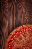 En färgrik partisk sammansättning av en brun korg med den röda vinbäret på en trätabell för mörk brunt Royaltyfri Foto