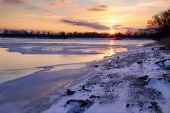 En färgrik purpurfärgad solnedgång över entäckt sjö i en nordlig stad Arkivbilder