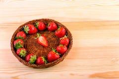 En färgrik sammansättning av en korg för mörk brunt står på en ljus trätabell med nya röda sunda jordgubbar Fotografering för Bildbyråer