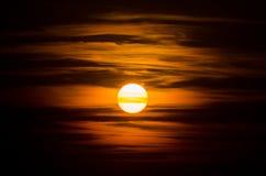 En färgrik solnedgång i molnen med en röd solcloseup Arkivfoton