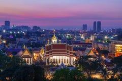 En färgrik solnedgång med en härlig sikt över Bangkok och en tempel framtill arkivfoto