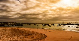 En färgstrand med små fartyg på horisonten Royaltyfri Fotografi