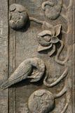 En fågel och blommor skulpterades på en pelare i borggården av en buddistisk tempel nära Hanoi (Vietnam) Arkivfoto
